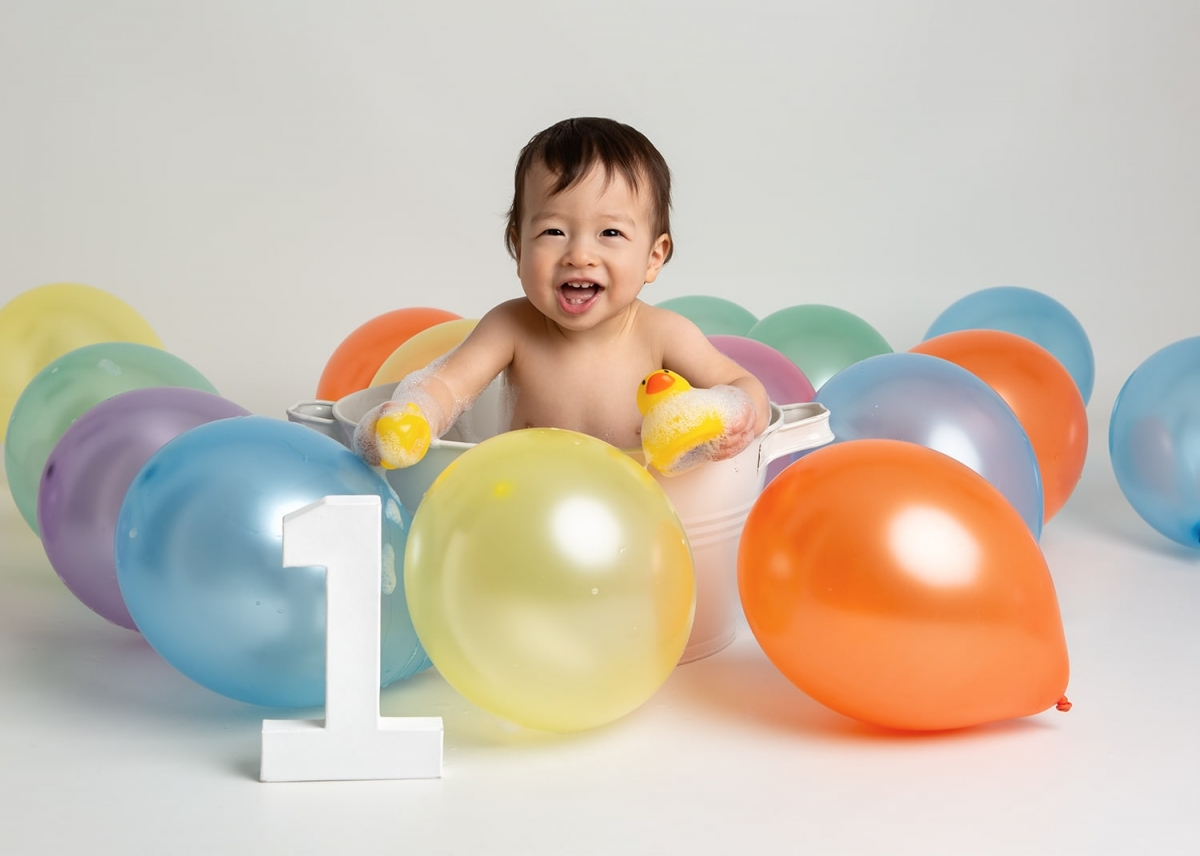 1 Year old baby in tub with balloons around the tub