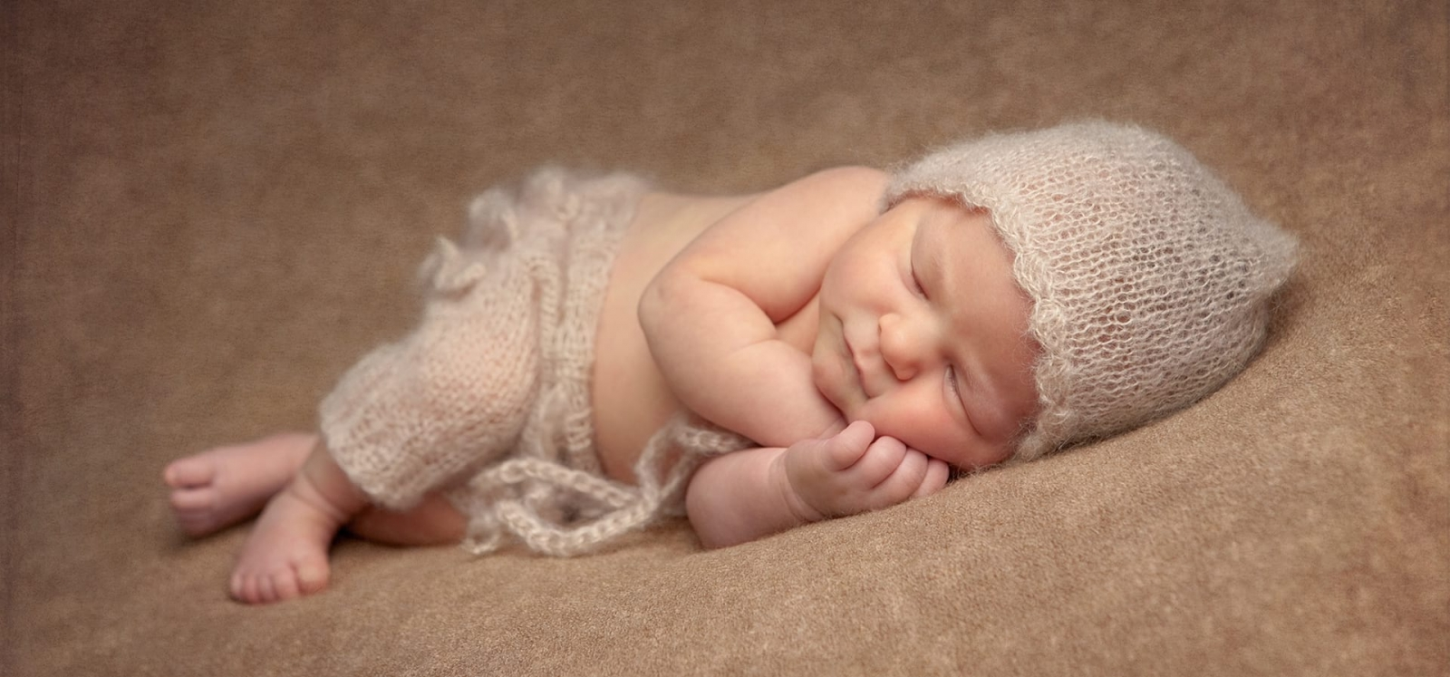 Newborn girl in side lying pose wearing a beige pant and hat set