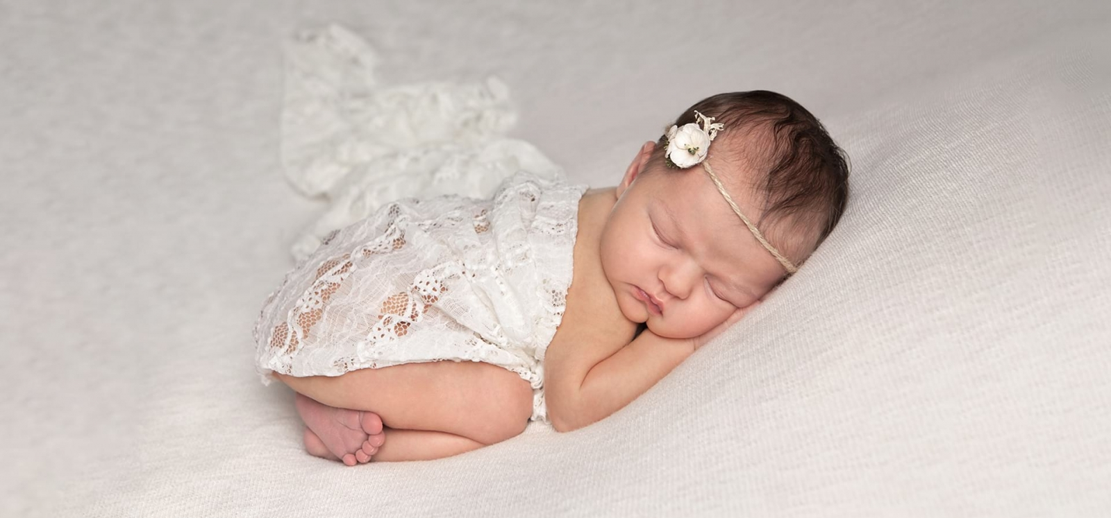 Newborn in tushy up position wearing a cream flower tie back and draped with cream lace