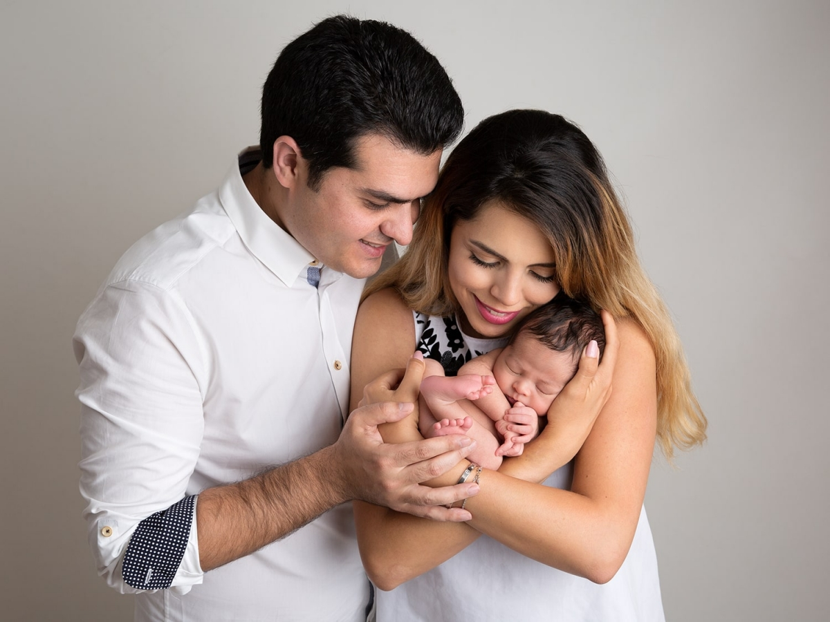 8 Day old baby boy with parents cradles in mother's arms