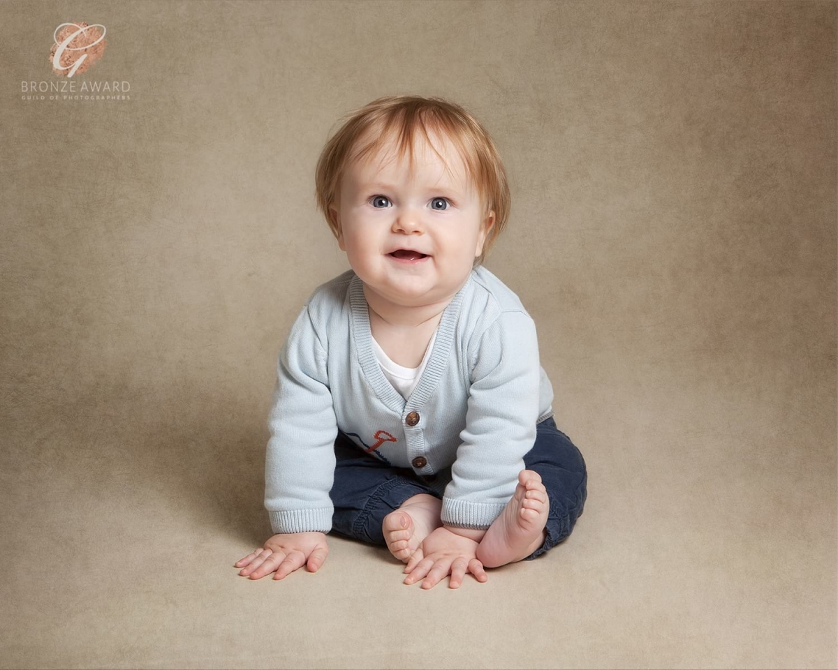 Bronze award for happy 7 month old sitting on a textured taupe backdrop
