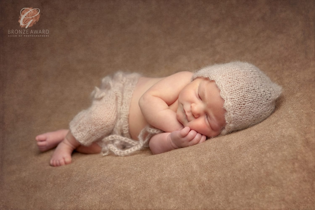 Bronze award for newborn baby girl wearing beige bonnet and pant set