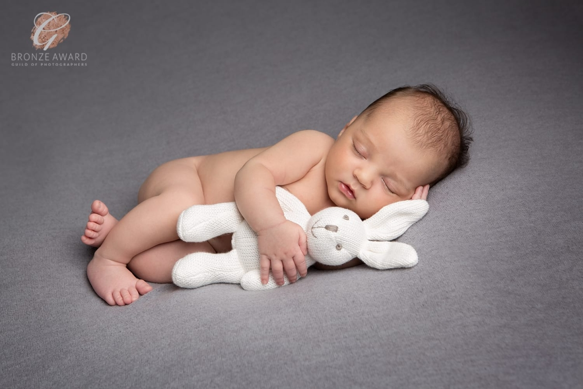 Bronze award for newborn photograph of baby clutching a white bunny on a grey blanket
