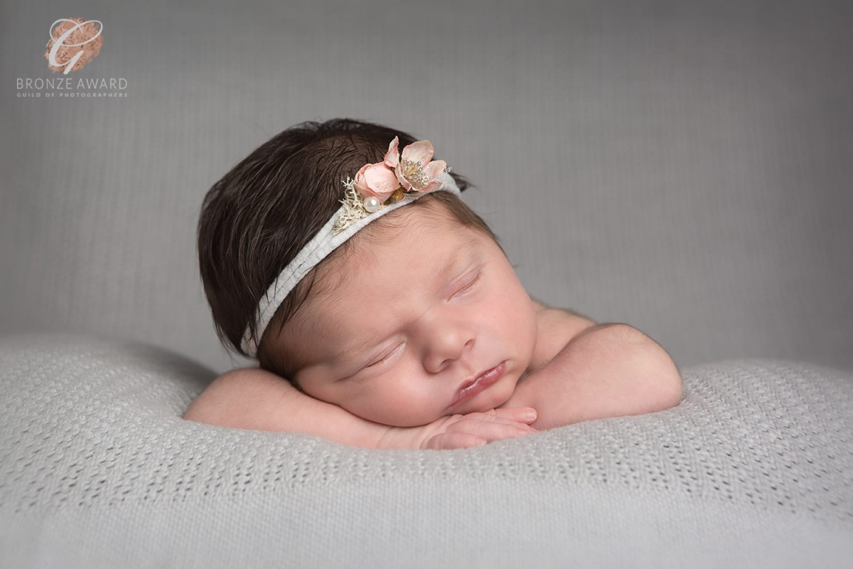 Bronze award for newborn facing forward lying on hands and wearing a grey tieback with a pink flower