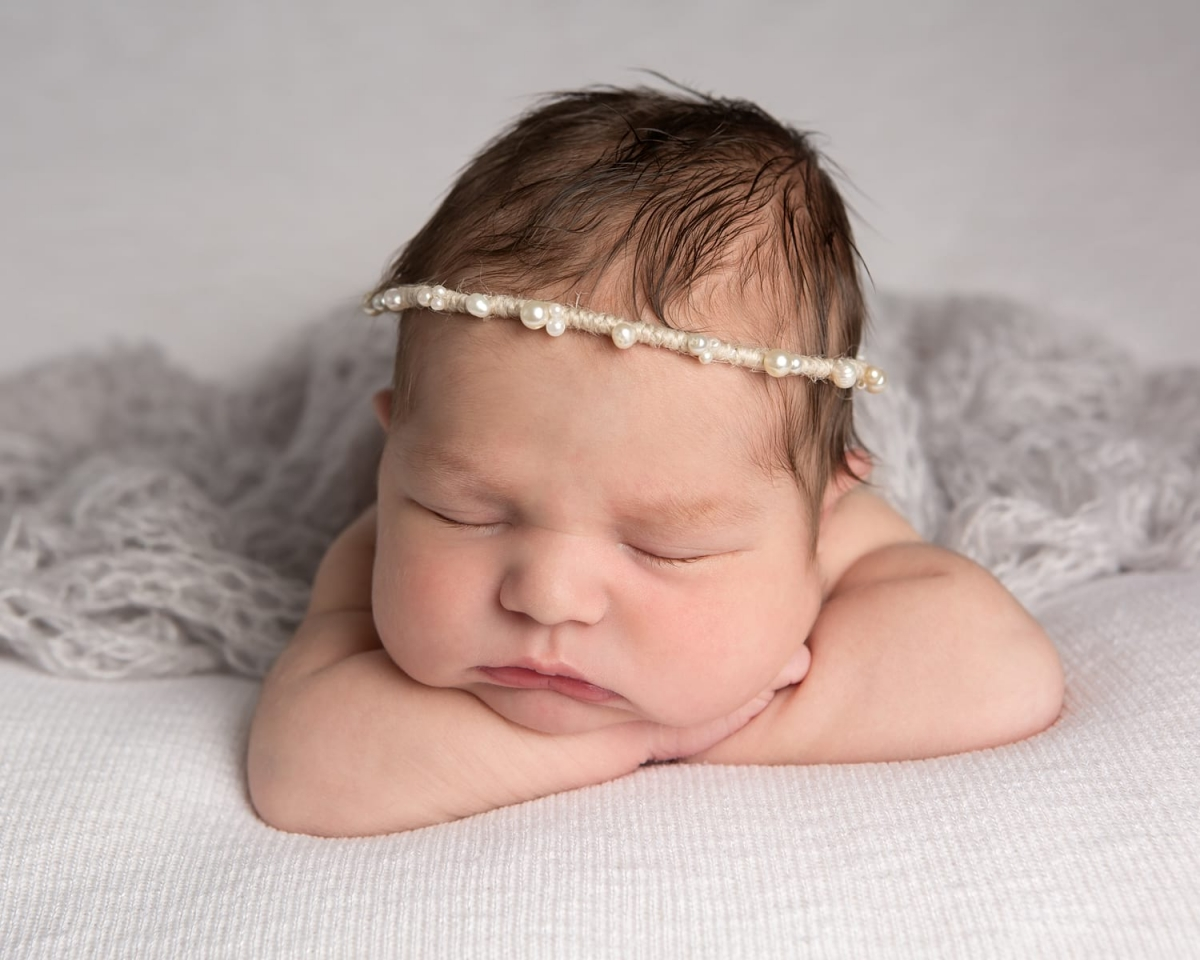 Newborn girl lying on hands wearing pearl hair band